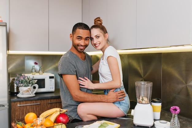 Foto des glücklichen paares in der küche. der ehemann legte seine frau in kurzen hosen auf den tisch. liebhaber, die sich umarmen. zeit zu hause teilen, auf gesichter lächeln.