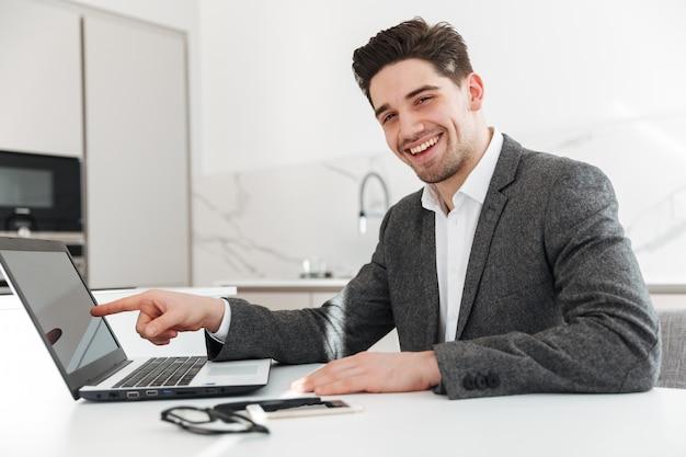 Foto des glücklichen sachlichen mannes, der finger auf bildschirm des laptops zeigt, während telearbeit von zu hause aus