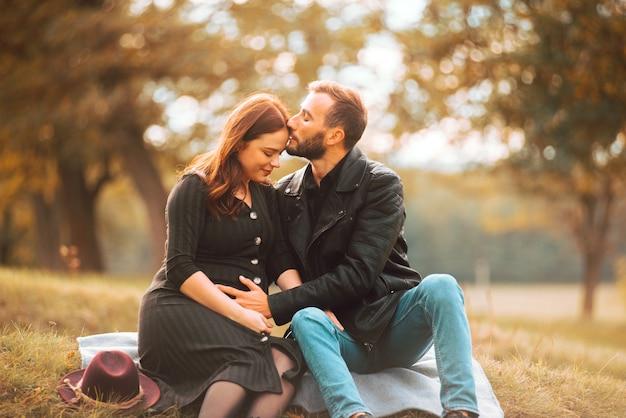 Foto des glücklichen schwangeren paares, das auf der bank im park sitzt, schöner stirnkuss