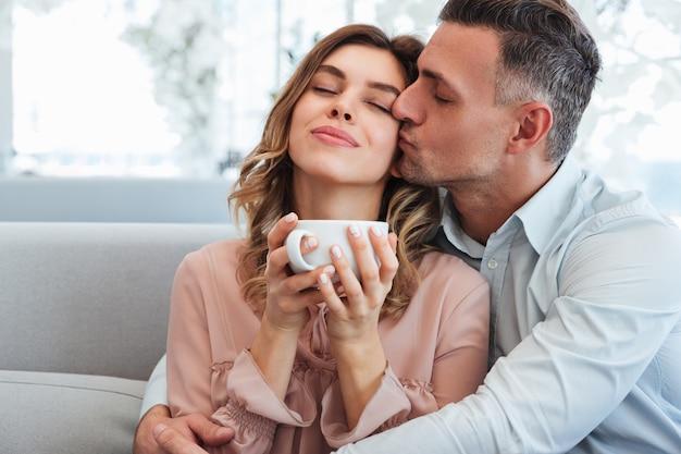 Foto des glücklichen zarten mannes und der frau, die umarmen und den aufenthalt zusammen im stadtcafé mit der tasse heißen tees genießen