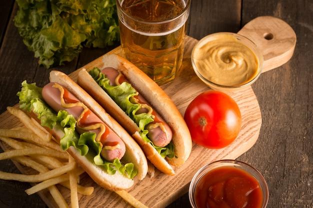 Foto des grills grillte hotdog mit gelbem senf und ketschup auf hölzernem. hotdogsandwich mit kartoffelpommes und soßen.