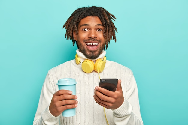 Foto des gutaussehenden fröhlichen mannes mit dreadlocks, hält modernes handy und kaffee zum mitnehmen, mit kopfhörern