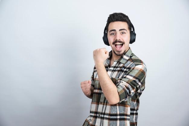 Foto des gutaussehenden kerls in den kopfhörern, die ein lied singen und tanzen.