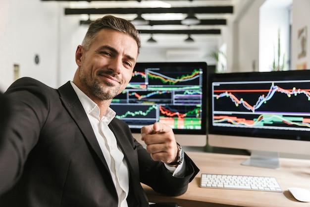 Foto des gutaussehenden mannes 30s, der anzug trägt, der selfie nimmt, während im büro am computer mit grafiken und diagrammen am bildschirm arbeitet