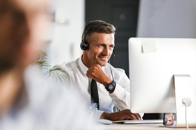 Foto des gutaussehenden mannes 30s, der bürokleidung und headset trägt und am computer im callcenter arbeitet