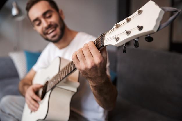 Foto des gutaussehenden mannes 30s, der lässiges t-shirt trägt, das akustische gitarre spielt, während auf sofa in wohnung sitzt
