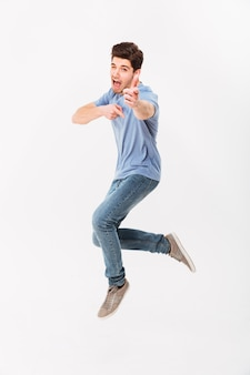 Foto des gutaussehenden mannes der 30er jahre in lässigem t-shirt und in jeans, die spaß haben und zeigefinger auf kamera zeigen, lokalisiert über weißer wand