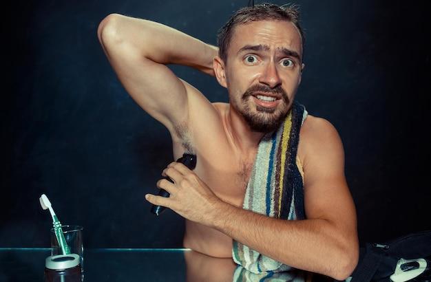 Foto des gutaussehenden mannes, der seine achselhöhle rasiert. der junge mann im schlafzimmer sitzt zu hause vor dem spiegel. konzept der menschlichen haut und des lebensstils