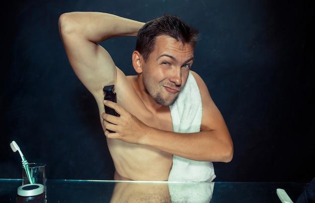 Foto des gutaussehenden mannes, der seine achselhöhle rasiert. der junge mann im schlafzimmer sitzt zu hause vor dem spiegel