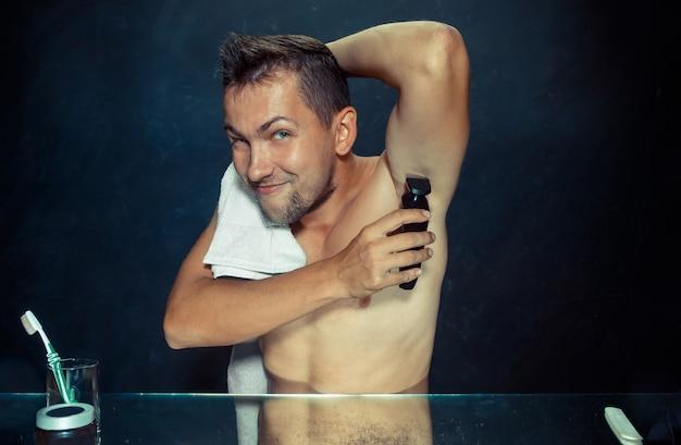 Foto des gutaussehenden mannes, der seine achselhöhle rasiert