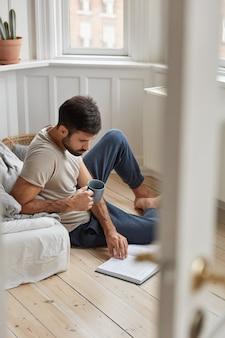 Foto des gutaussehenden mannes entspannt sich mit literatur, genießt das entspannen zu hause, konzentriert sich auf das lesen, sitzt auf dem boden, hält tasse