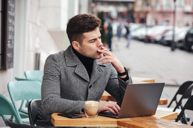 Foto des gutaussehenden mannes in rauchender zigarette des grauen mantels und in trinkendem cappuccino beim im café draußen stillstehen