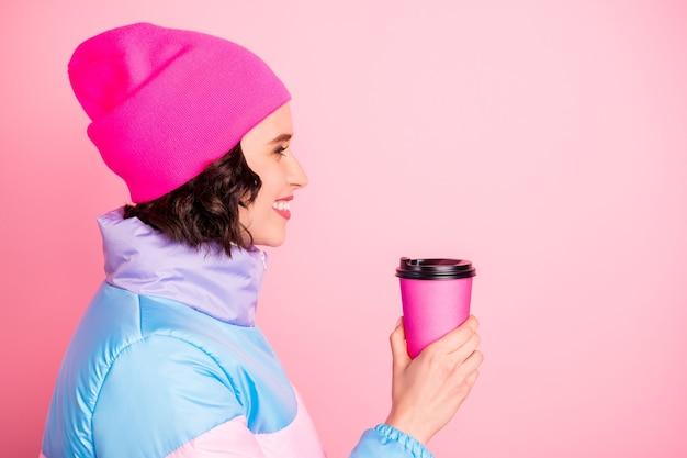 Foto des heißen getränks der schönen dame, die hände für den besten freund hält, tragen warmen farbigen mantel lokalisierten rosa hintergrund