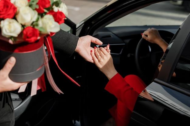 Foto des höflichen mannes mit blumenstrauß, der geschäftsfrau im roten anzug hilft, aus dem auto auf dem parkplatz im freien herauszukommen