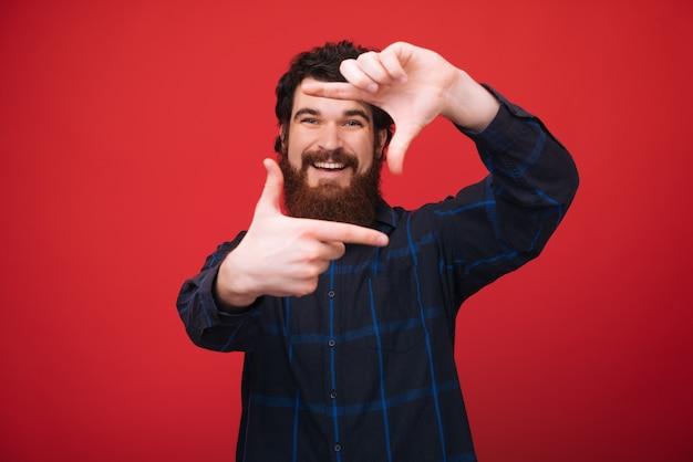 Foto des hübschen bärtigen mannes, der über der roten wand steht und einen fotorahmen mit den fingern tut, ein foto machend