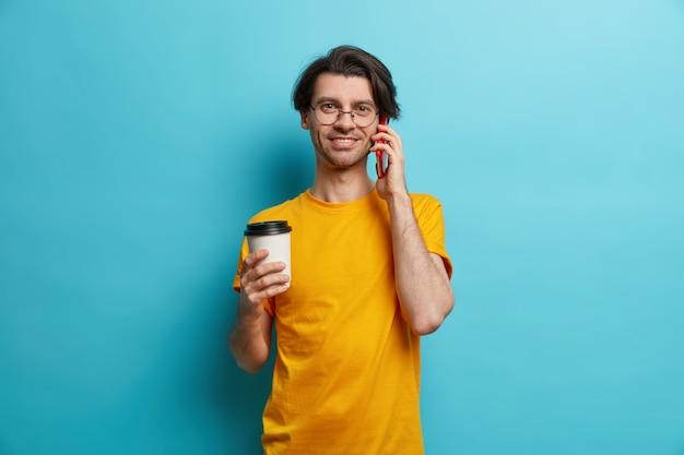 Foto des hübschen erwachsenen europäischen mannes hat telefongespräch über smartphone trinkt kaffee, um zu gehen