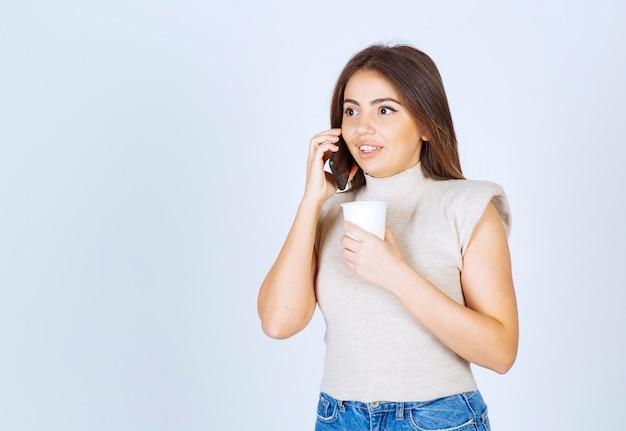 Foto des hübschen frauenmodells, das am telefon steht und spricht.