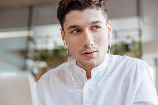 Foto des hübschen jungen mannes, der im weißen hemd unter verwendung des laptopcomputers gekleidet wird, während er musik hört. coworking. sieh zur seite.
