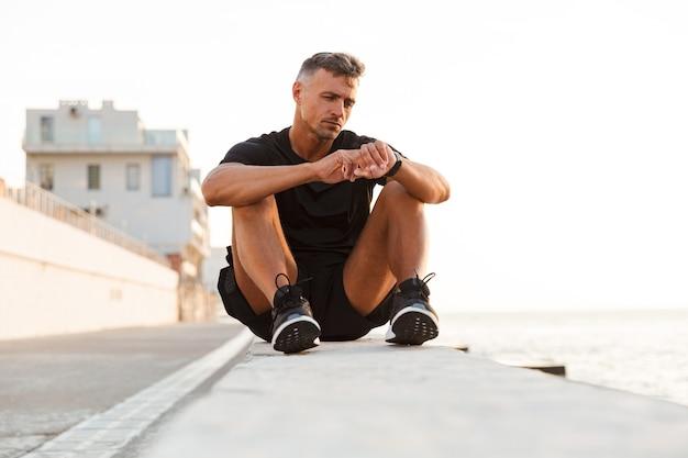 Foto des hübschen kaukasischen mannes 30s im trainingsanzug, der auf brüstung der promenade nahe der küste sitzt und handgelenk smartwatch betrachtet