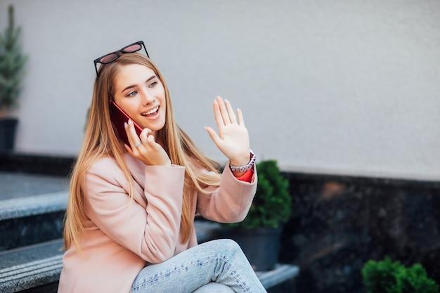 Foto des hübschen mädchens verbringt ihre zeit auf der straße und spricht mit ihrem telefon. treffen sie sich mit jemandem.