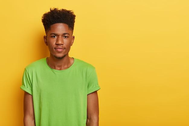 Foto des hübschen teenagers mit dunkler haut, lockiger frisur, trägt lässiges grünes t-shirt, sieht mit ruhigem ernstem ausdruck aus