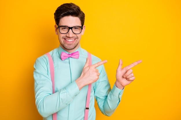 Foto des hübschen trendoutfitgeschäftsmanns selbstsichere händefinger, die seite leeren raum zeigen neuheit tragen spezifikationen spezifikationen hemd hosenträger fliege isoliert gelbe farbe hintergrund