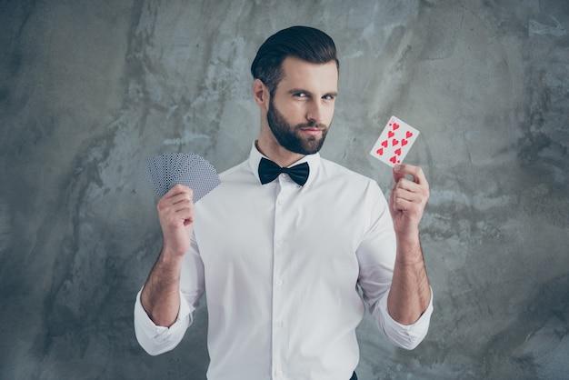Foto des intelligenten klugen kartenspielers, der sie zeigt, fokussiert, indem sie verschiedene kartenanzüge demonstrieren, die über graue betonwand isoliert werden