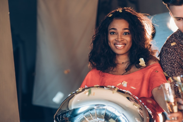 Foto des jungen afroamerikanermädchens mit silbernem ballon in den händen, die nahe dem freund und dem lächeln innen stehen. konfetti in der luft