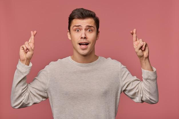 Foto des jungen attraktiven fröhlichen mannes im leeren langen ärmel, machen sie einen wunsch, hofft auf viel glück, schaut in die kamera, steht isoliert über rosa hintergrund mit gekreuzten fingern.