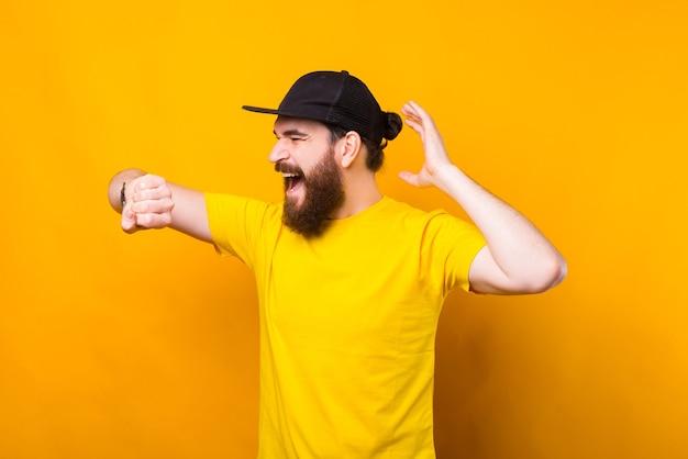 Foto des jungen bärtigen hipster-mannes, der angst bei smartwatch schaut