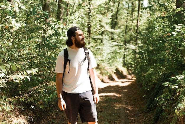 Foto des jungen bärtigen mannes, der im wald während der sommerzeit, reisekonzept wandert.