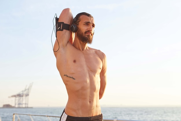 Foto des jungen gutaussehenden sportlichen mannes mit bart. genießen sie den morgen, machen sie dehnübungen, haben sie eine muskulöse körperform, hören sie lieblingsmusik über kopfhörer.