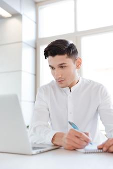 Foto des jungen konzentrierten mannes, der in weißem hemd gekleidet wird und laptop-computer benutzt, während er notizen im notizbuch schreibt. coworking. computer betrachten.