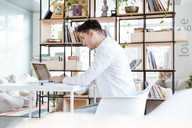 Foto des jungen konzentrierten mannes im weißen hemd mit laptop-computer gekleidet. coworking. laptop betrachten.