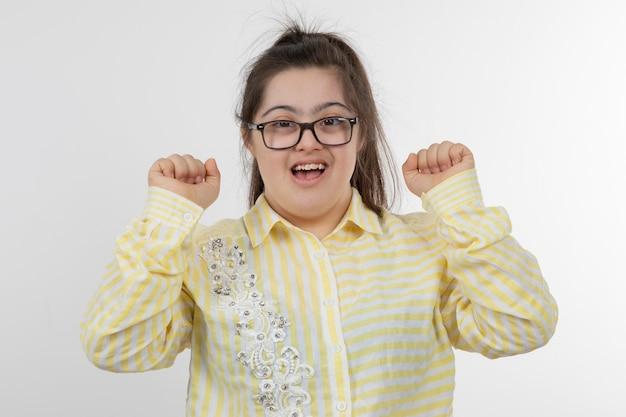 Foto des jungen mädchens mit einem down-syndrom, das gelbes kariertes hemd aufwirft, das aufwirft