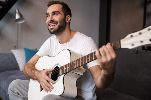 Foto des jungen mannes 30s, der lässiges t-shirt trägt, das akustische gitarre spielt, während auf sofa in wohnung sitzt