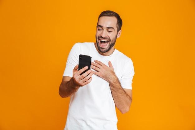 Foto des jungen mannes 30s in der freizeitkleidung, die smartphone lächelt und hält, lokalisiert