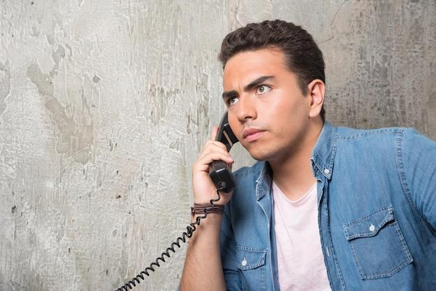 Foto des jungen mannes, der am telefon spricht und auf stuhl sitzt. hochwertiges foto