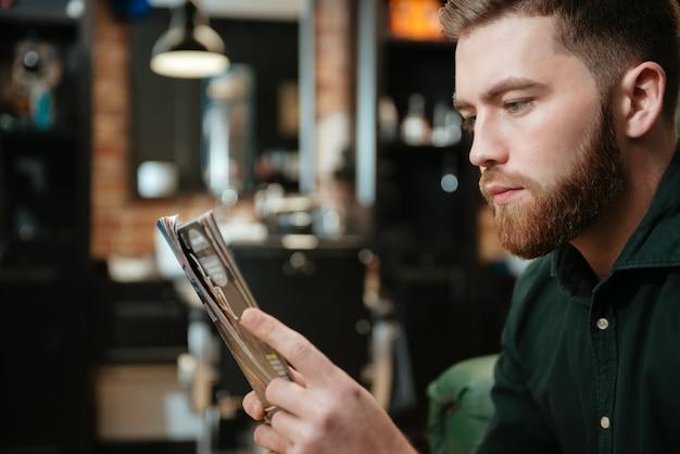 Foto des jungen mannes, der im sessel im friseursalon sitzt und zeitschrift liest.