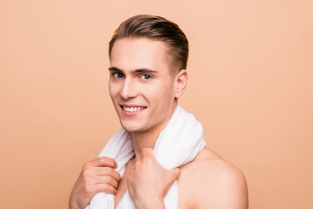 Foto des jungen mannes, der lokalisiert auf pastellbeige aufwirft