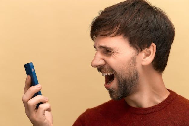 Foto des jungen mannes mit bart, der pullover trägt, der im zorn und im schock schreit, das handy benutzt, sich über informationen auf dem bildschirm frustriert fühlt und gegen beige wand aufwirft