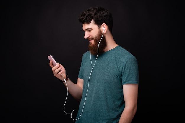 Foto des jungen mannes mit bart, der smartphone betrachtet, während über schwarzem hintergrund steht