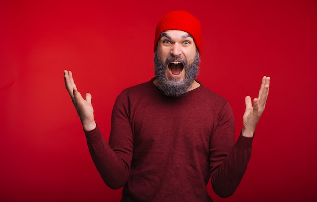 Foto des jungen mannes überrascht, die kamera über rotem raum betrachtend