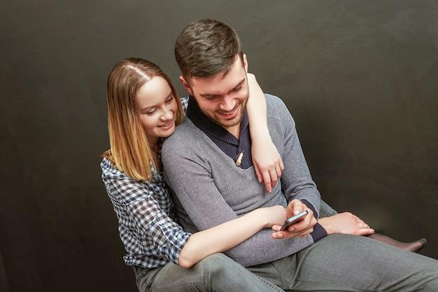 Foto des jungen paares, das gegen schwarzen hintergrund sitzt und ein smartphone benutzt
