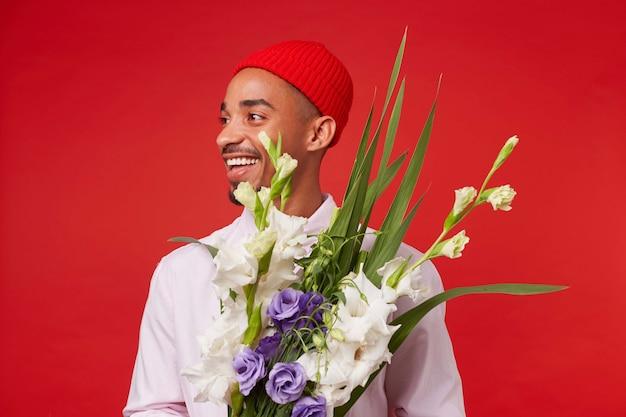 Foto des jungen positiven dunkelhäutigen mannes, trägt in weißem hemd und rotem hut, schaut weg und lächelt, hält blumenstrauß, steht über rotem hintergrund.