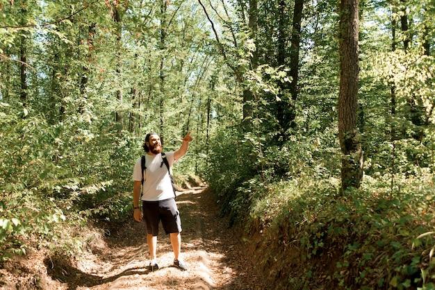 Foto des jungen reisenden, der in der mitte des waldes steht und weg zeigt.