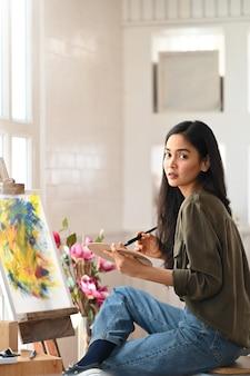 Foto des jungen schönen künstlers, der einen pinsel hält und auf leinwand malt