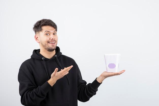 Foto des jungen schönen mannes, der fernsehserie und popcorn-eimer betrachtet