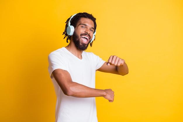 Foto des jungen schwarzen kerls, der aufgeregt mit offenem mund tanzt, trägt kopfhörer weißes t-shirt isoliert gelber farbhintergrund