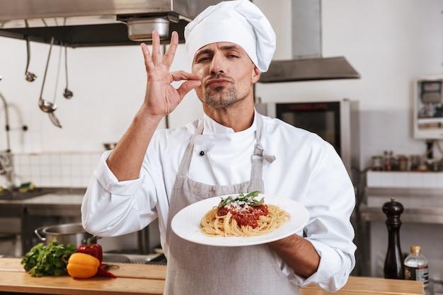 Foto des kaukasischen männlichen chefs in der weißen uniform, die platte mit mahlzeit hält